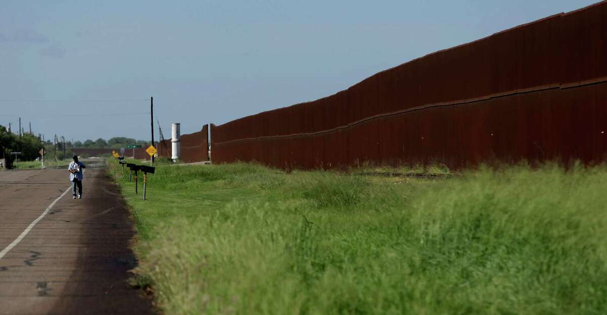 In this Sept. 4, 2012, photo, a man retrieves his mail near the U.S.-Mexico border fence in Brownsville, Texas. Since 2008, hundreds of landowners on the border have sought fair prices for property that was condemned to make way for the fence, but many of them received initial offers that were far below market value. (AP Photo/Eric Gay)