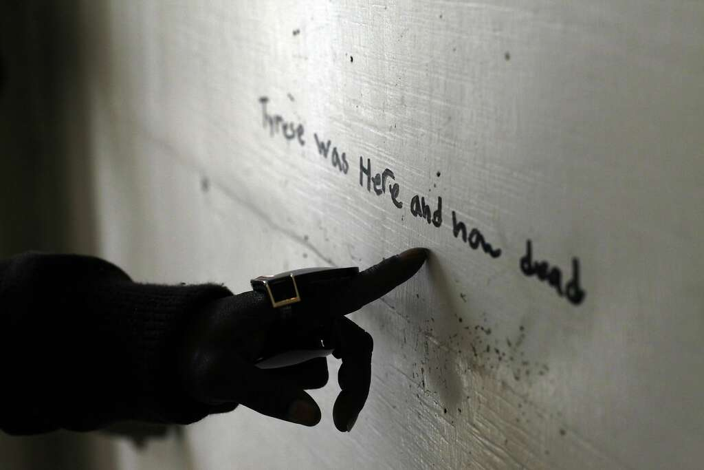 Tammy Hill points out a message that was written on the wall in the hallway,. Photo: Lacy Atkins, The Chronicle