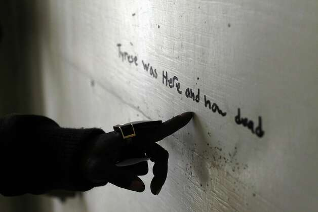 Tammy Hill points out a message that was written on the wall in the hallway, Tuesday October 8, 2013, at the Hacienda Public Housing Complex in Richmond, Calif. Photo: Lacy Atkins, The Chronicle