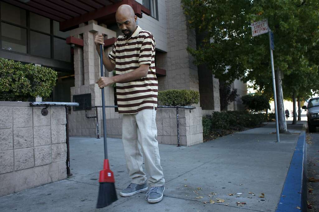 Jeff Likely, resident manager of the Nevin Plaza Public Housing sweeps the front sidewalk in prepara, The Chronicle