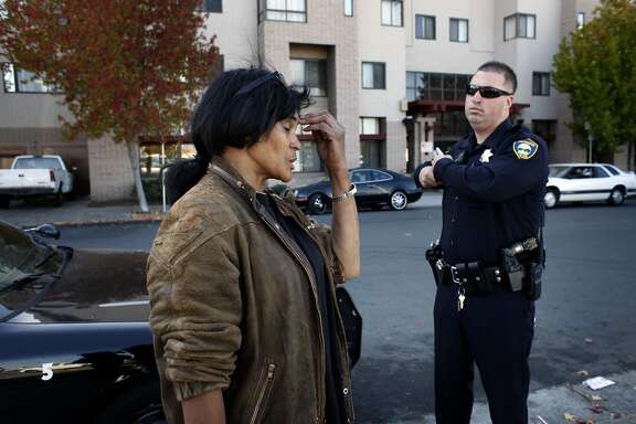 Bridgette Monique Rollins tries to explain to Richmond Police Officer Ojo that she didn't want any trouble, but that she just wanted her Supplement Security Income check, Friday November 1, 2013, outside of Nevin Plaza Public Housing Complex in Richmond, Calif. She was evicted last month and believed management had kept her check when the locks were changed.