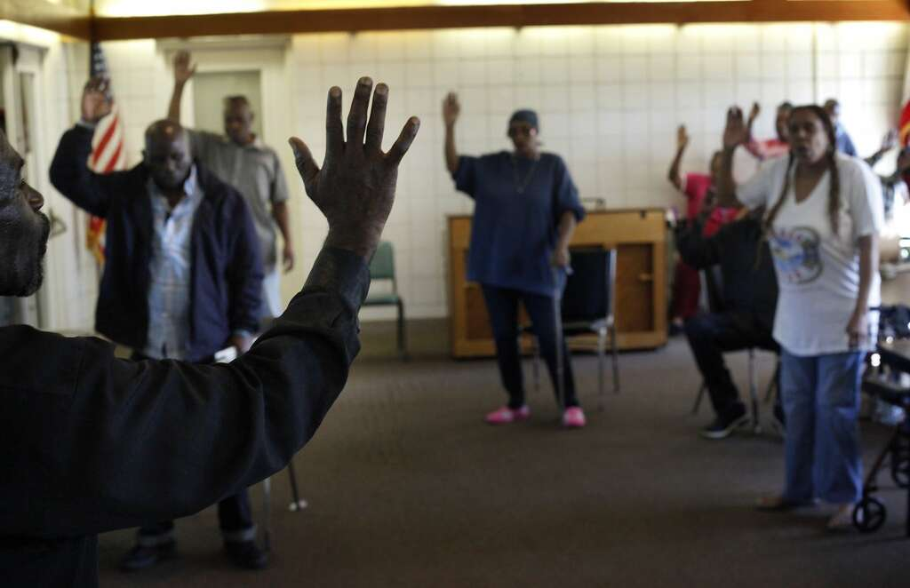 Preacher Eddie Williams, 62, leads the residents of Nevin Plaza public  housing in prayer at afterno. Photo: Lacy Atkins, The Chronicle