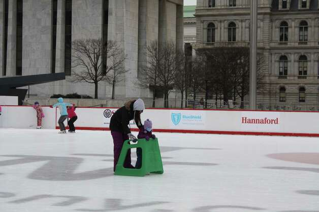 An instructor from the Hudson Mohawk Figure Skating Club helps a first-time skater navigate the ice at a Learn to Skate Clinic presented by BlueShield at the Empire State Plaza Ice Rink on Jan. 25.  (Kaitlyn Oudt)