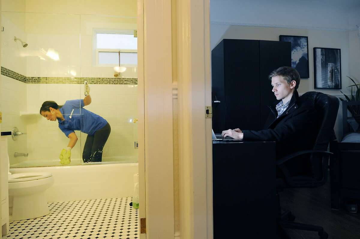 Handybook operations manager Tristan Zier works from home as Katia Nunez, left, a maid hired through Handybook's marketplace, cleans the bathroom in his home in San Francisco, CA Friday, February 7, 2014. Handybook is an online house-cleaning and repair website new to the Bay Area.