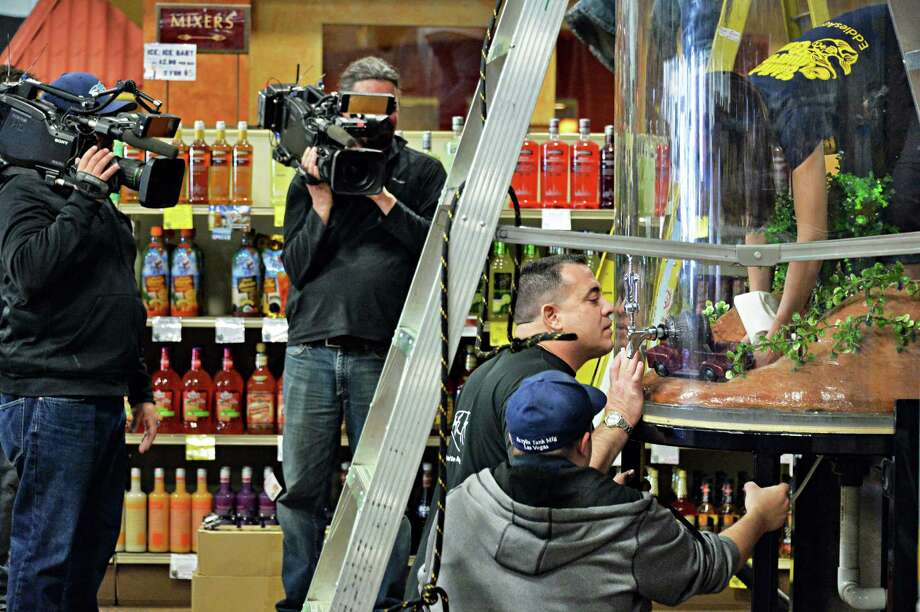 Animal Planet's 'Tanked' star Wayde King, center, works on a fish tank installation as the TV show films an episode at All-Star wines at Latham Farms Friday Feb. 7, 2014, in Colonie, NY.  (John Carl D'Annibale / Times Union) Photo: John Carl D'Annibale / 00025669A