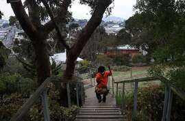 "Jamal Kile, 11, races his younger brother down the Joy St. stairs on their way home in Bernal Heights Feb. 6, 2014 in San Francisco, Calif. Nancy Statler, who lives nearby, likes to walk her dog Sasha down the stairs street, ""I love these stairs,"" Statler said, ""it's in the middle of the city like a little oasis."""