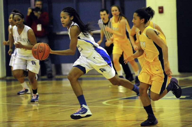 Albany's Mylah Chandler, center, drives up court  during their basketball game against Troy on Frida