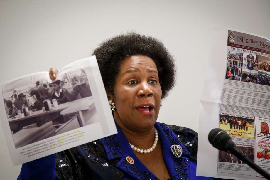 """Sheila Jackson Lee (D-Houston) holds posters in support of saving the Southmore Station Post Office during her Town Hall Meeting to """"Save Our Post Offices"""" on Jan. 11, 2014 in Houston. (Michael Paulsen 