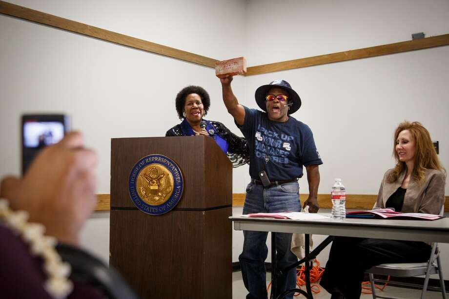 "Brady V. Randall, center, a retired 34-year veteran of the U.S. Postal Service, holds a brick in the air from the original Southmore Station post office as U.S. Rep. Sheila Jackson Lee, left, observes during the congresswoman's Town Hall Meeting to ""Save Our Post Offices"" on Jan. 11, 2014 in Houston. (Michael Paulsen 