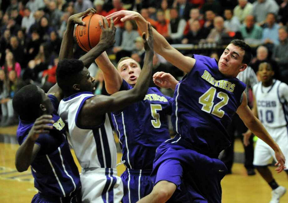 CCHS's Raiquis Harris, second from left, struggles for the ball against CBA's Dan Owens, left, Nick Marini, center, and Paul Corradi during their basketball game on Friday, Feb. 7, 2014, at Catholic Central High in Troy, N.Y.  (Cindy Schultz / Times Union) Photo: Cindy Schultz / 00025677A