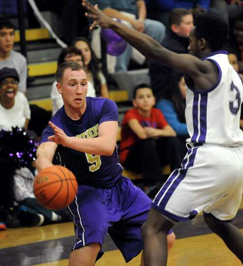 CBA's Nick Marini, left, passes the ball around CCHS's Brian Brooks during their basketball game on