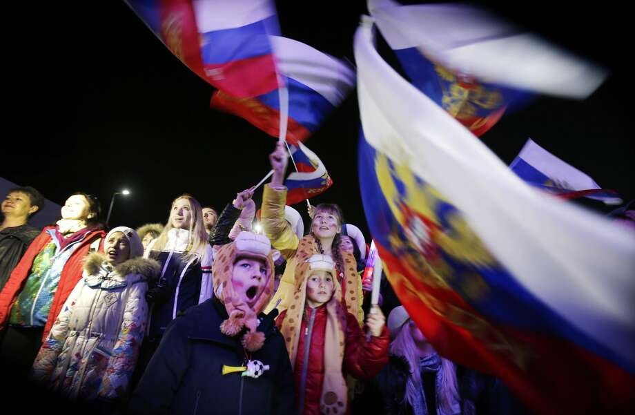 A Russian child yawns while others wave the national flag as the Russian national anthem is played during the live telecast of the 2014 Winter Olympics opening ceremony, Friday, Feb. 7, 2014, in downtown Sochi, Russia. (AP Photo/Wong Maye-E) Photo: Associated Press