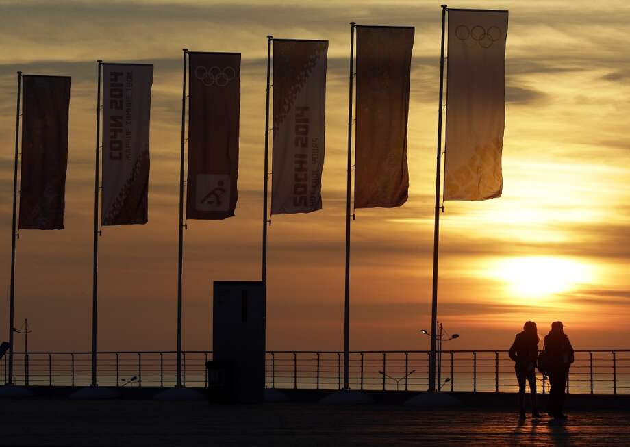 People stand near Olympic flags as they watch the sun set over the Black Sea at the 2014 Winter Olympics, Saturday, Feb. 8, 2014, in Sochi, Russia. (AP Photo/Mark Humphrey) Photo: Associated Press
