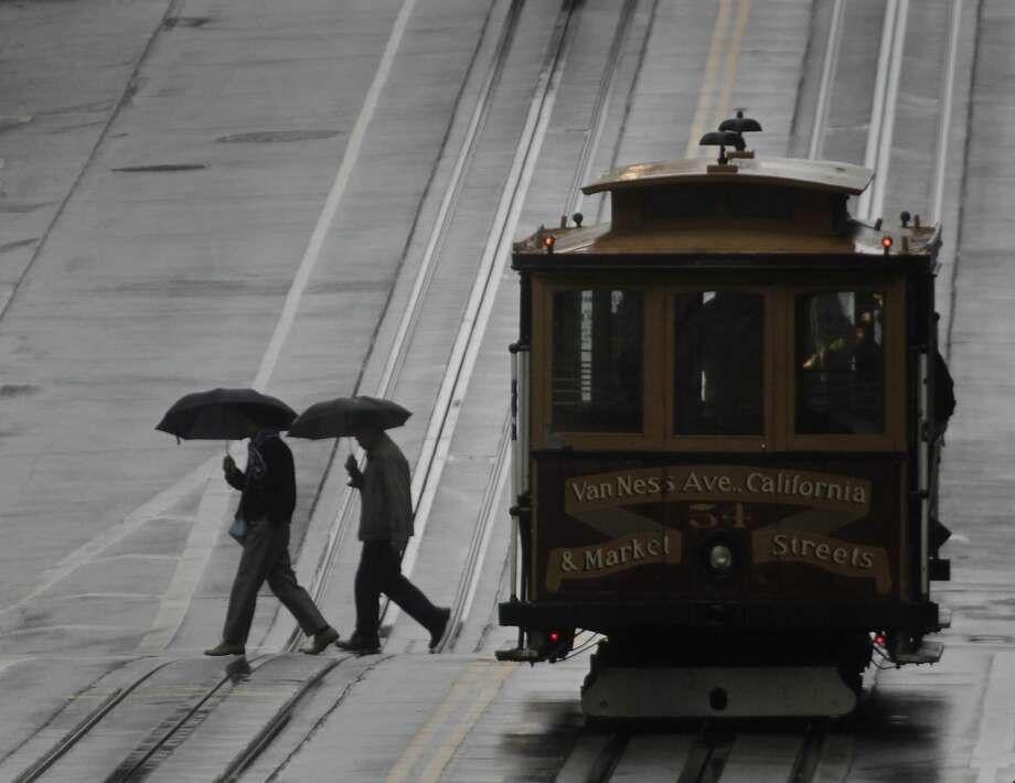 Pedestrians cross California Street in the rain in San Francisco, Calif. on Saturday, Feb. 8, 2014.  Photo: Paul Chinn, The Chronicle