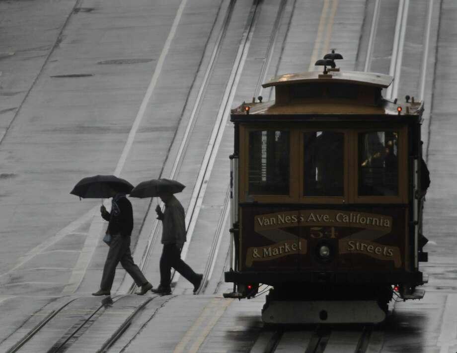 Pedestrians cross California Street in the rain in San Francisco, Calif. on Saturday, Feb. 8, 2014.  Photo: Paul Chinn, The Chronicle