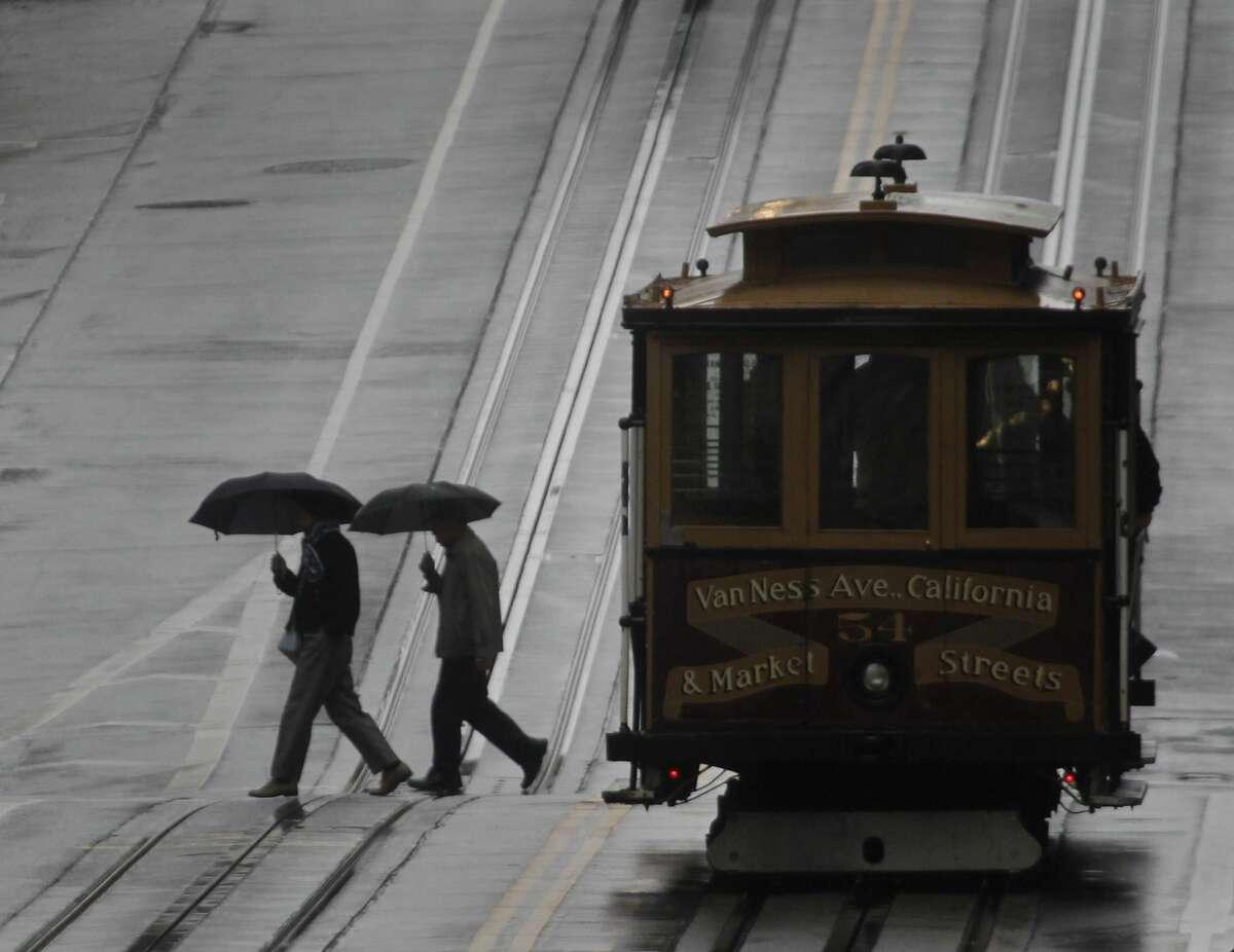 Pedestrians cross California Street in the rain in San Francisco, Calif. on Saturday, Feb. 8, 2014.