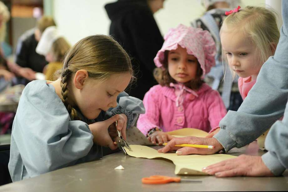 Bethel children Grace Mary, left, 7, Lillian Mancusi, center, 5, and Madison Lavelle, 5, make prarie bonnets out of paper during the Bethel Historical Society's celebration of author Laura Ingalls Wilder at the 1842 Second Meeting House in Bethel, Conn. Saturday, Feb. 8, 2014.  The children read stories, churned butter and also made handkerchief dolls, button necklaces and fresh-squeezed lemonade. Photo: Tyler Sizemore / The News-Times