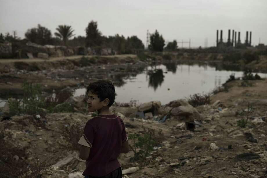 A Bedouin boy stands near an open pool of sewage in the garbage filled Wadi Gaza in the central Gaza Strip on November 27, 2013, as the silhouette of the Gaza Strip power plant is seen in the background. Gaza is suffering from the most serious fuel crisis in its history, with the shortages badly affecting the operation of hospitals, water and sanitation plants, businesses and private homes, which suffer daily power outages of up to 16 hours. AFP PHOTO/MARCO LONGARIMARCO LONGARI/AFP/Getty Images Photo: MARCO LONGARI / AFP