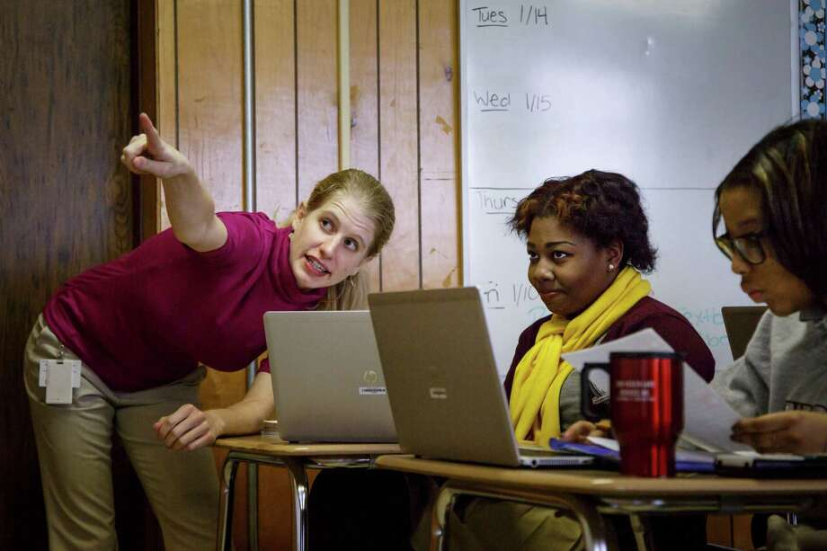 Teacher Heather York helps Crystal Hymes, right, with pre- calculus at the Young Women's College Preparatory Academy. Photo: Michael Paulsen, Staff / © 2014 Houston Chronicle