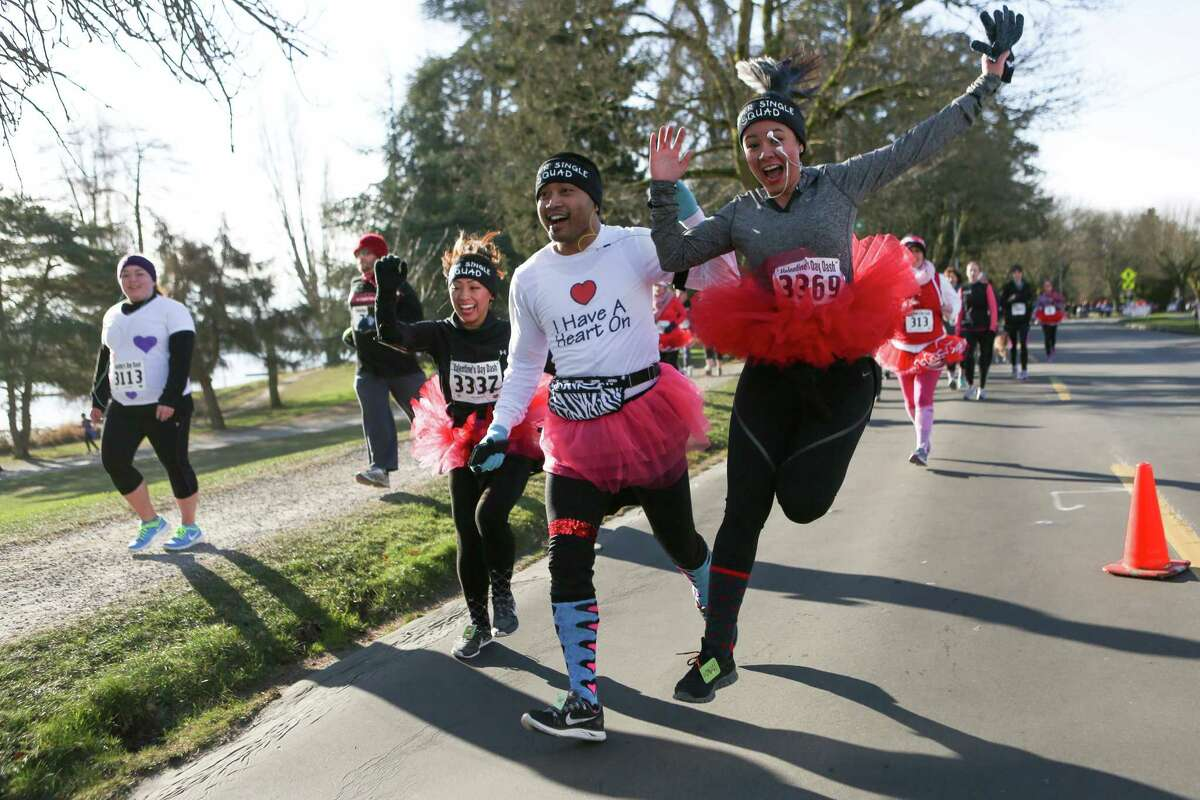 Mary Angela Munoz, Andrew Souksavath and Clarisse Zayas run during the Valentine's Day Dash 5K on Saturday, February 8, 2014 at Green Lake. Thousands of runners participated in the annual pre-Valentine's Day event.