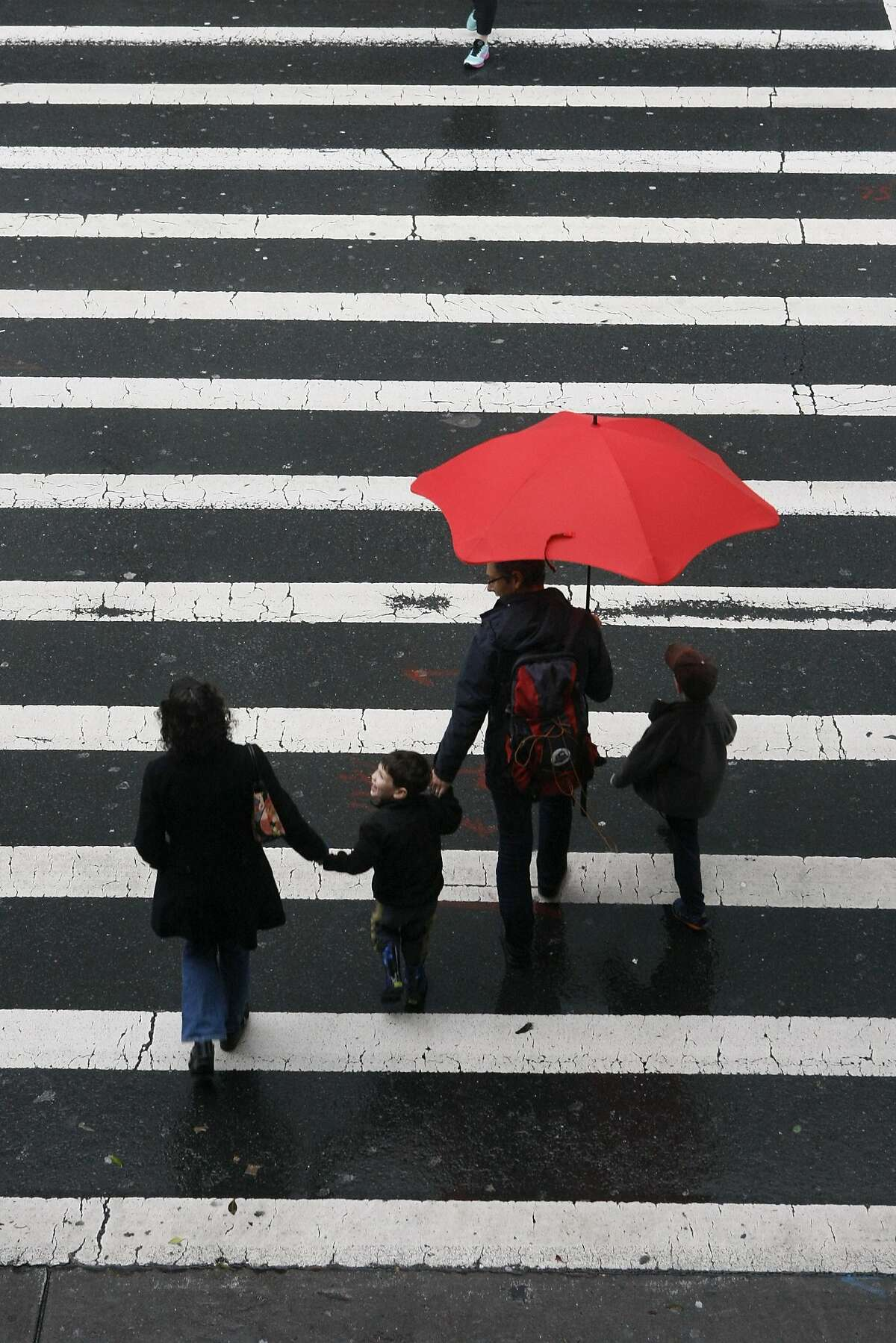 A family braves the wet weather on a rainy February 8, 2014 in San Francisco, Calif.