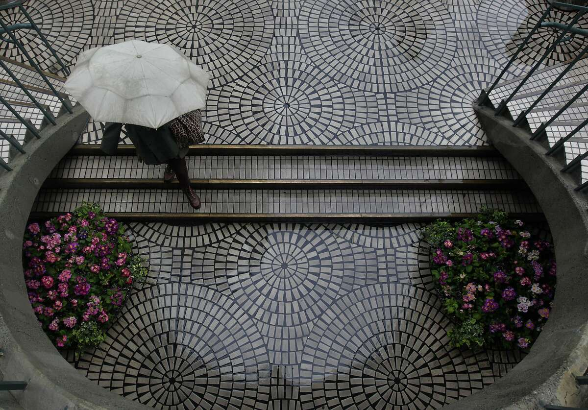 A woman stays dry under an umbrella at the Embarcadero Center in San Francisco, Calif. on Saturday, Feb. 8, 2014. The Bay Area is getting doused this weekend in one of the biggest storms in over a year.