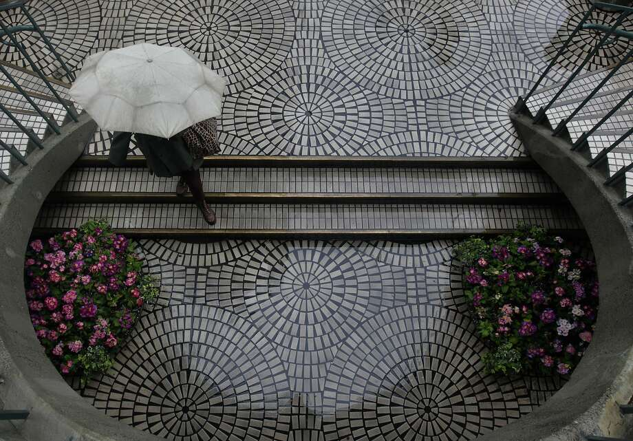 A woman stays dry under an umbrella at the Embarcadero Center in San Francisco, Calif. on Saturday, Feb. 8, 2014. The Bay Area is getting doused this weekend in one of the biggest storms in over a year. Photo: Paul Chinn, The Chronicle