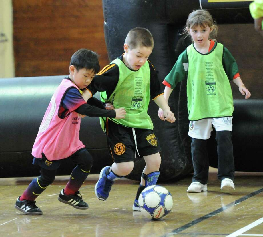 """At center, Brayden Senft, 5, of Greenwich, attempts to clear the ball from his team's offensive zone while fending off an opponent, at left, during the Town of Greenwich Department of Parks and Recreation's """"Saturday Indoor Soccer with Aldwin,""""  a youth soccer program, at the Greenwich Civic Center, Saturday, Feb. 8, 2014. Photo: Bob Luckey / Greenwich Time"""