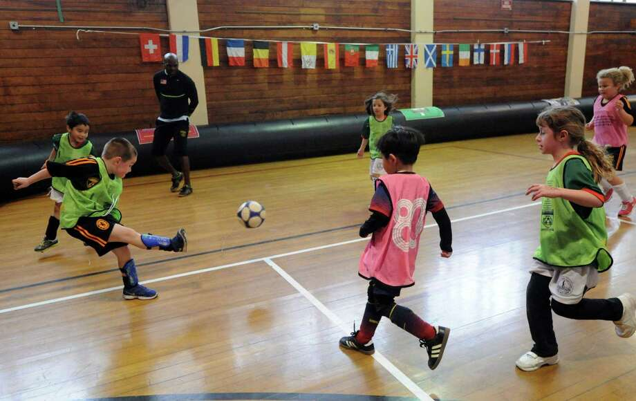 "Brayden Senft, 5, of Greenwich, advances the ball with a kick during the Town of Greenwich Department of Parks and Recreation's ""Saturday Indoor Soccer with Aldwin,""  a youth soccer program, at the Greenwich Civic Center, Saturday, Feb. 8, 2014. Photo: Bob Luckey / Greenwich Time"