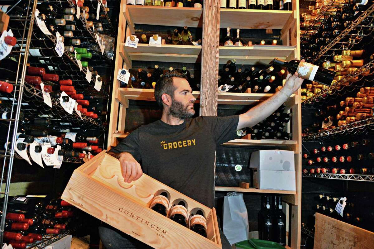 Vic Christopher, co-owner of Lucas Confectionery, cellars bottles of Continuum, a California boutique wine, at his 2nd Street wine bar Friday Feb. 7, 2014, in Troy. (John Carl D'Annibale / Times Union)