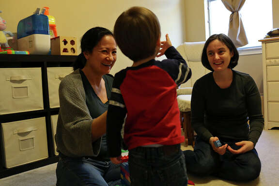 Cleo DeLeon, left, and Nicole Dimetman play with their son at their home in Austin on Saturday, Feb. 8, 2014.