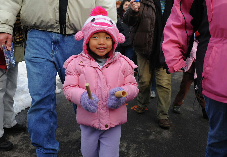 Delaney Stachacz, 4, of Oxford, takes part in the Asian New Year Celebration held at Beardsley Zoo in Bridgeport, Conn. on Saturday February 8, 2014. Delaney walks in the dragon parade around the zoo with other participants by banging two sticks, which makes noise to chase away any evil spirits. 2014 marks the Year of the Horse. Photo: Christian Abraham / Connecticut Post