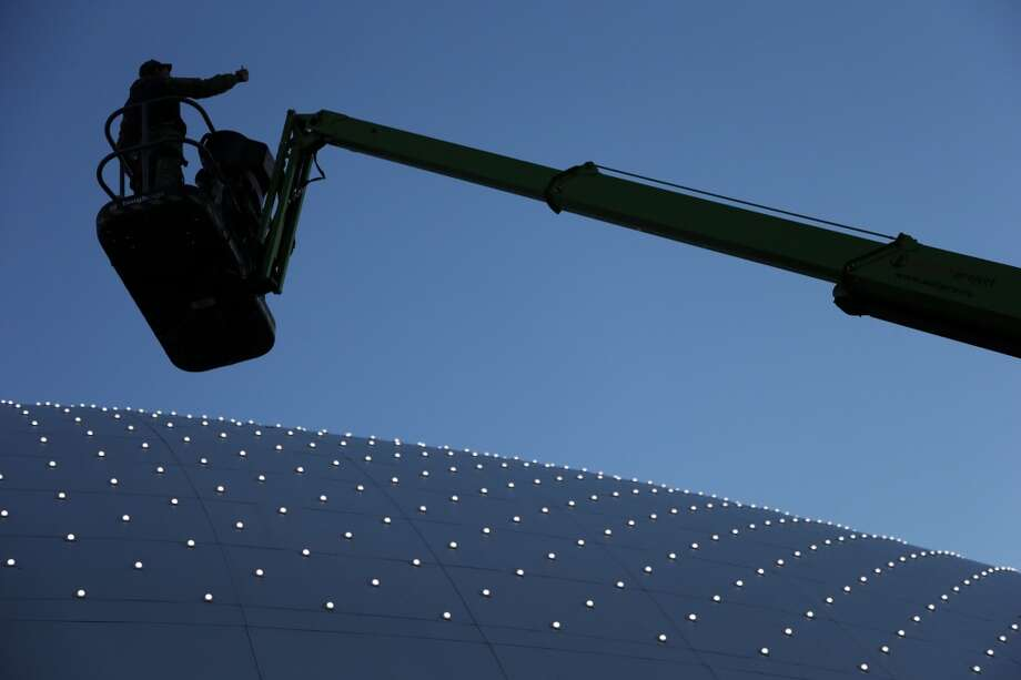 A worker pauses to take a photo of himself as he washes windows at the  Bolshoy Ice Dome hockey arena at the 2014 Winter Olympics, Saturday, Feb. 8, 2014, in Sochi, Russia. (AP Photo/Mark Humphrey) Photo: Mark Humphrey, Associated Press