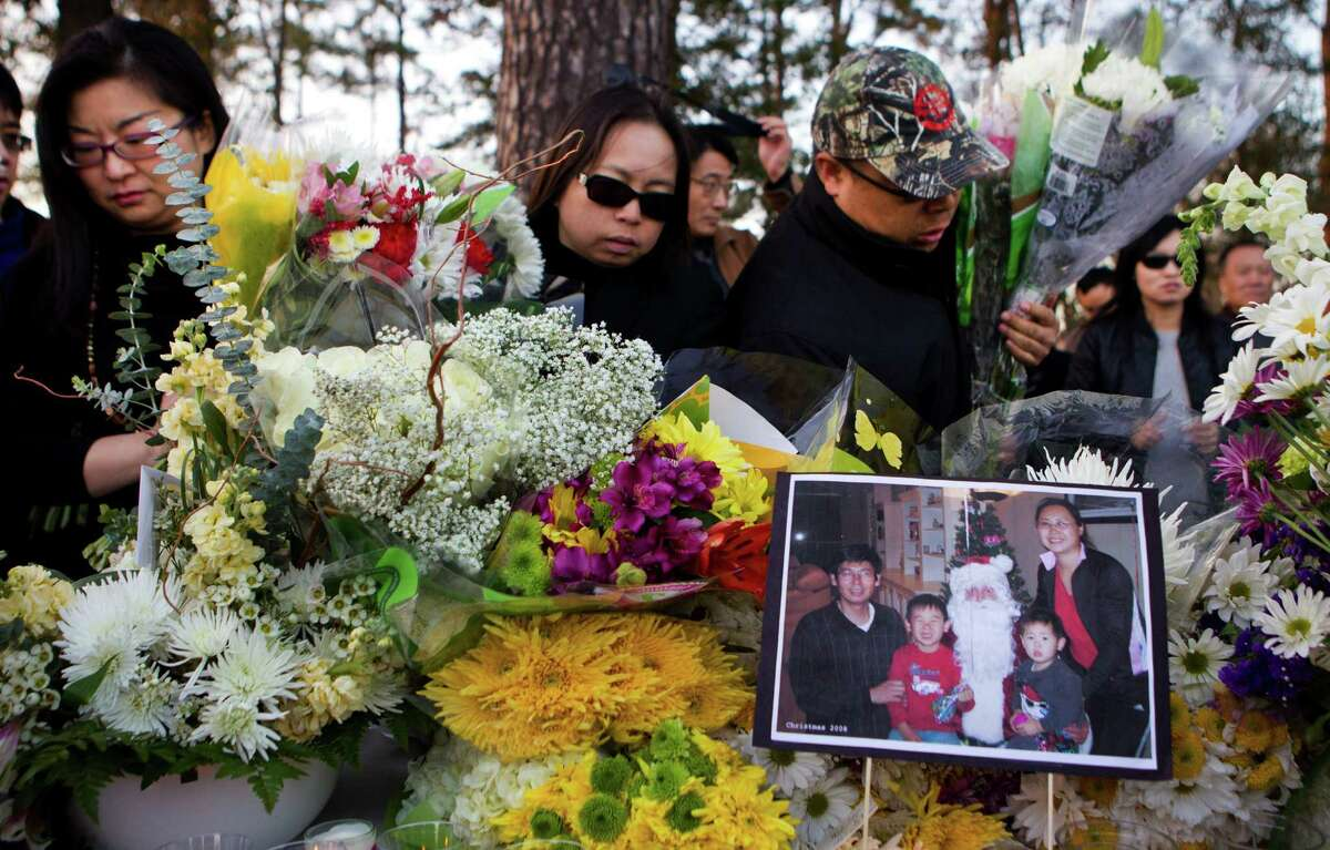 Mourners gather flowers to carry to the home of the family of four shot to death at their home in Cypress during a vigil held in their honor Saturday, Feb. 8, 2014, in Houston. A vigil was organized by the Houston Chinese Alliance for victims Maoye Sun, 50, Mei Xie, 49, and their two sons, Timothy Xie Sun, 9, and Titus Xiao Sun, 7.
