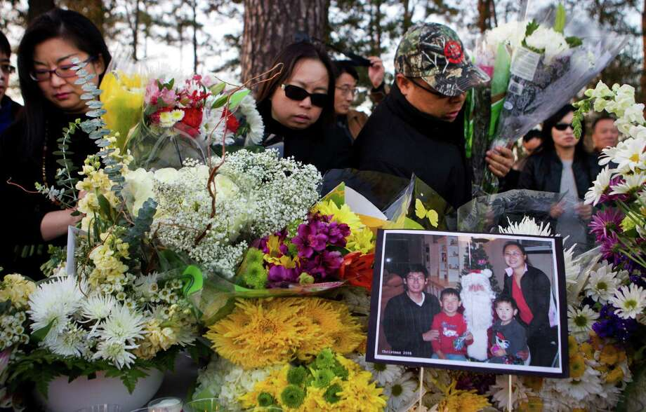 Mourners gather flowers to carry to the home of the family of four shot to death at their home in Cypress during a vigil held in their honor Saturday, Feb. 8, 2014, in Houston. A vigil was organized by the Houston Chinese Alliance for victims Maoye Sun, 50, Mei Xie, 49, and their two sons, Timothy Xie Sun, 9, and Titus Xiao Sun, 7. Photo: Brett Coomer, Houston Chronicle / © 2014 Houston Chronicle