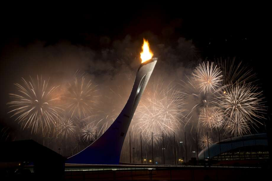 Fireworks explode behind the Olympic torch after it was lit at end of the opening ceremony for the 2014 Winter Olympics in Sochi, Russia, Friday, Feb. 7, 2014. (AP Photo/Bernat Armangue) Photo: Associated Press