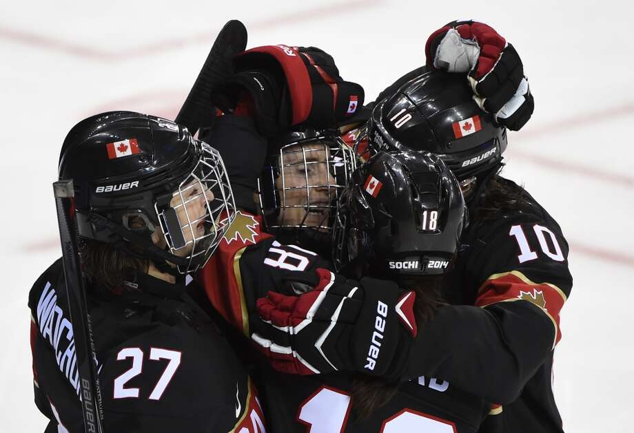 Canada's Hayley Wickenheiser (2nd L) celebrates with team mates after scoring during the Women's Ice Hockey Group A match between Canada and Switzerland at the Shayba Arena during the Sochi Winter Olympics on February 8, 2014. Canada won 5-0.    AFP PHOTO / JONATHAN NACKSTRANDJONATHAN NACKSTRAND/AFP/Getty Images Photo: AFP/Getty Images