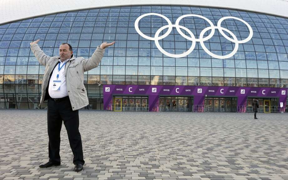 A man poses for a photograph as if he is holding up the Olympic rings on the Bolshoy Ice Dome hockey arena at the 2014 Winter Olympics, Saturday, Feb. 8, 2014, in Sochi, Russia. (AP Photo/Mark Humphrey) Photo: Associated Press