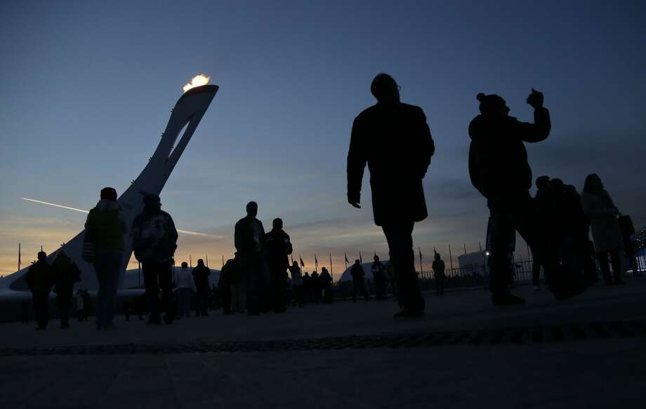 Visitors to Olympic Park stroll around the base of the Olympic flame at the  2014 Winter Olympics in Sochi, Russia, Saturday, Feb. 8, 2014. (AP Photo/Julie Jacobson) Photo: Associated Press