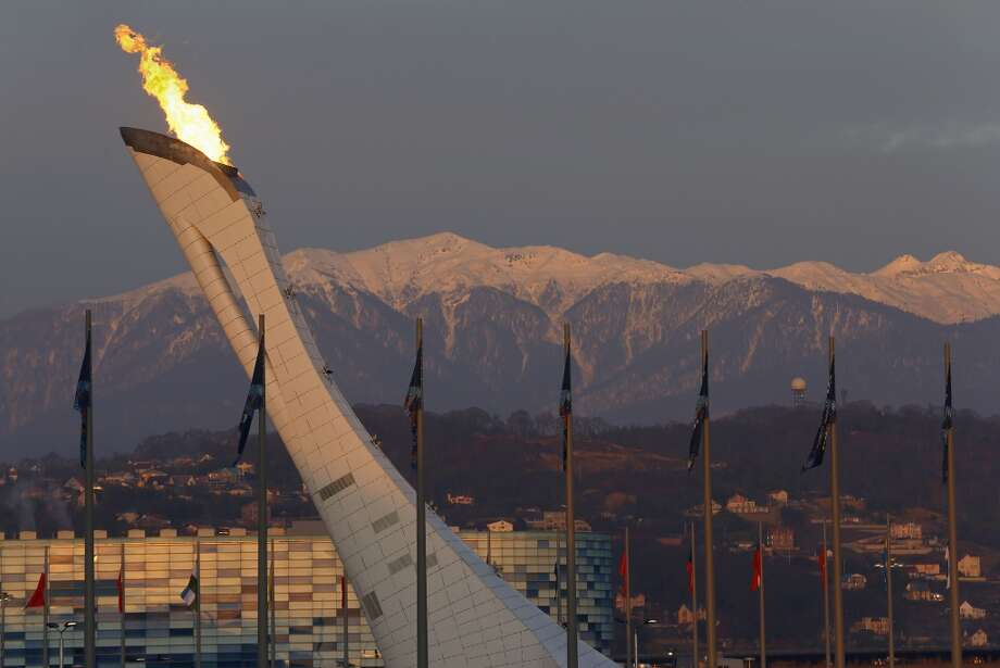 Alpenglo settles on the Caucasus mountains at sunset as the Olympic flame burns above Olympic Park during the 2014 Winter Olympics in Sochi, Russia, Saturday, Feb. 8, 2014. (AP Photo/Julie Jacobson) Photo: Associated Press