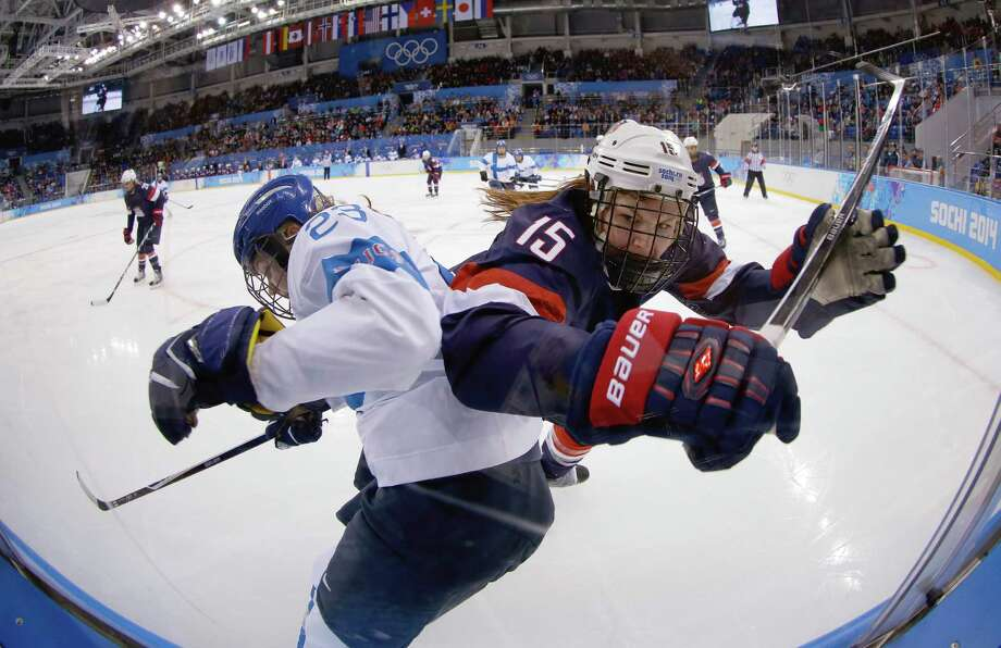 Nina Tikkinen of Finland and Anne Schleper of the United States battlers from control of the puck against the glass during the second period of the women's ice hockey game at the Shayba Arena during the 2014 Winter Olympics, Saturday, Feb. 8, 2014, in Sochi, Russia. (AP Photo/Matt Slocum) Photo: Matt Slocum, Associated Press / AP