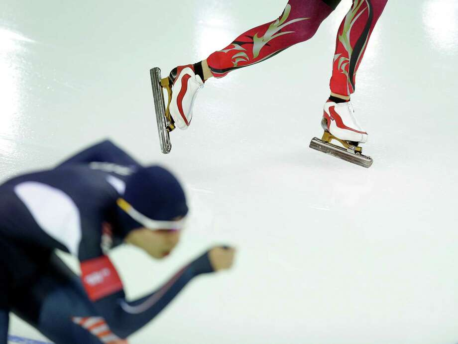 Patrick Beckert of Germany, top, and South Korean speedskater Lee Seung-hoon compete in the men's 5,000-meter speedskating race at the Adler Arena Skating Center during the 2014 Winter Olympics in Sochi, Russia, Saturday, Feb. 8, 2014. (AP Photo/Pavel Golovkin) Photo: Pavel Golovkin, Associated Press / AP