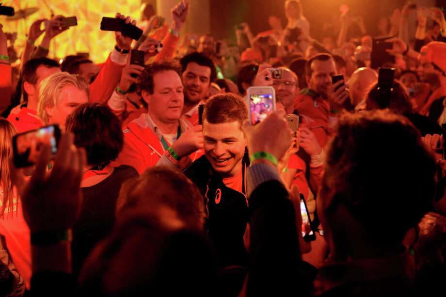 Under orange lighting, gold medallist Sven Kramer of the Netherlands walks through a crowd of cheering fans after winning the gold in the men's 5,000-meter speedskating race  at the 2014 Winter Olympics in Sochi, Russia, Saturday, Feb. 8, 2014. Kramer set a new Olympic record in the race. (AP Photo/Matt Dunham) Photo: Matt Dunham, Associated Press / AP