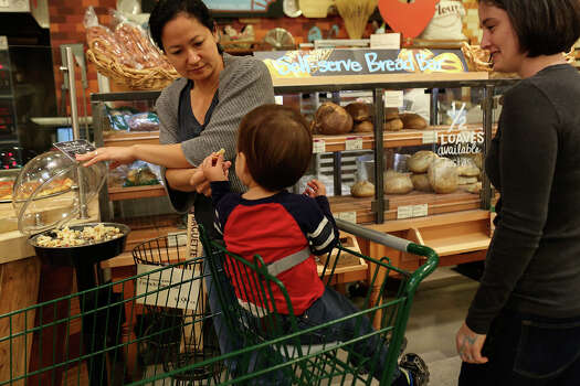 Cleo DeLeon, left, and Nicole Dimetman try samples while shopping with their son at Whole Foods in Austin on Saturday, Feb. 8, 2014. Photo: Lisa Krantz / San Antonio Express-News