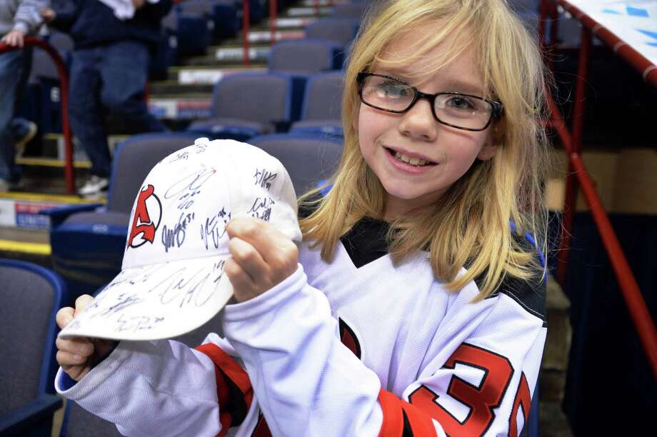 Ten-year-old Albany Devils fan Jordan Wedenbine of Albany shows off her player-autographed hat before Saturday's game against the Manchester Monarchs at the Times Union Center Jan. 11, 2014, in Albany, N.Y.  (John Carl D'Annibale / Times Union) Photo: John Carl D'Annibale / 00025290A