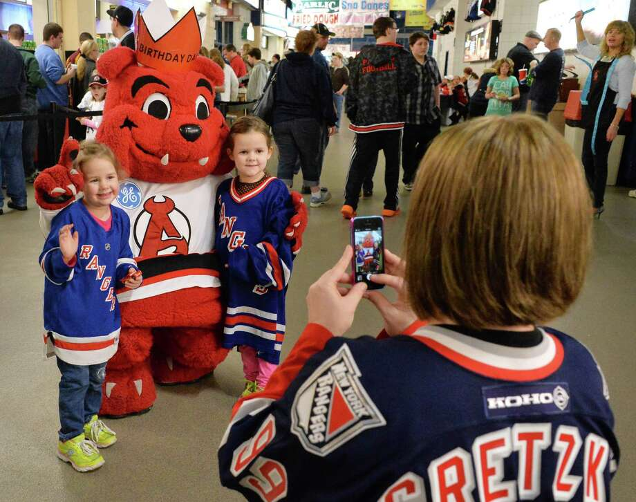 Daniella Richardson, at right, of Niskayuna takes a snapshot of daughters Molly, 3, left, and Chelsea, 5 as they pose with Albany Devils' mascot, Devil Dawg, before Saturday's game against the Manchester Monarchs at the Times Union Center, Jan. 11, 2014, in Albany, NY.  (John Carl D'Annibale / Times Union) Photo: John Carl D'Annibale / 00025290A