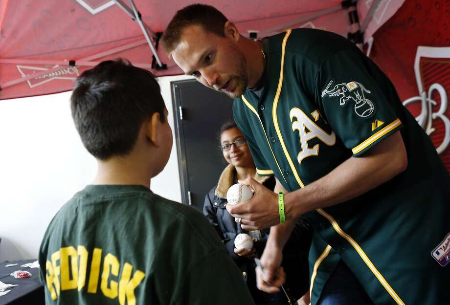 New A's closer Jim Johnson signs a ball for Gio Martinez of Pittsburg at the A's FanFest. Photo: Carlos Avila Gonzalez, The Chronicle