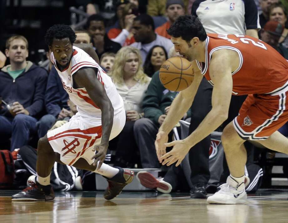 Pat Beverley, left, and ZaZa Pachulia reach for a loose ball. Photo: Jeffrey Phelps, Associated Press