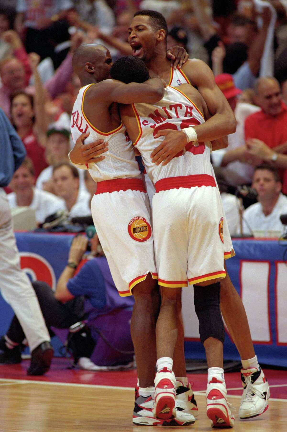 Guards Vernon Maxwell, left, and Kenny Smith and forward Robert Horry share a group hug after the Rockets beat the New York Knicks for the first of two consecutive NBA championships.