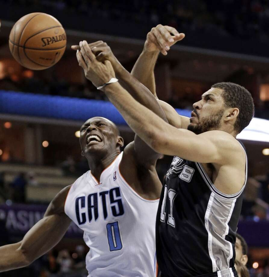 Charlotte Bobcats' Bismack Biyombo (0) and San Antonio Spurs' Jeff Ayres (11) battle for a rebound during the first half of an NBA basketball game in Charlotte, N.C., Saturday, Feb. 8, 2014. (AP Photo/Chuck Burton) Photo: Associated Press